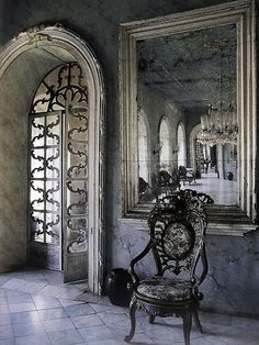 Wow, look at this incredible home! To have hallways like this to even decorate in such a manner! Th arched doorways with intricate glass doors and aged silver framed mirrors as well as crystal chandeliers. And the chairs!!