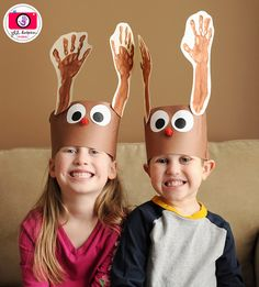 Handprint reindeer antlers! (brown construction paper, white/black/off-white cardstock, brown paint, red pompoms, 2 popsicle sticks, glue, scissors, and paper punches