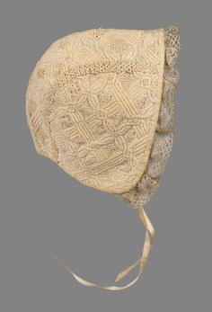 Infant's cap, probably The Netherlands, 18th century. Cream white cotton, interlacing all-over quilted pattern with details in punched holes and French knots. Bobbin lace around face, two narrow ribbon ties.