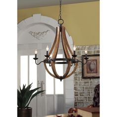 Candelabra style holders in dramatic black encircle the curvy, wood frame of this charming light fixture. The multi-light chandelier is elegantly detailed to infuse your living space with rustic sophistication.