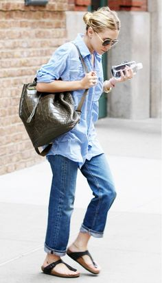 Ashley Olsen wears a chambray shirt, boyfriend jeans and a crocodile printed backpack with her Birkenstock sandals.