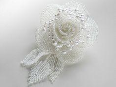 ホワイトのビーズで編んだぷらぶらリーフ付き薔薇ビーズコサージュ。花びらにパールを添えました。