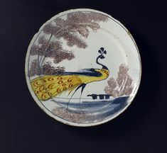 Plate of tin-glazed earthenware painted and 'sponged' in colours with a peacock in a landscape: English, Bristol, c. 1720.