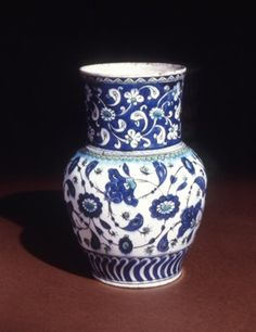 Vase. Curved flutes and flower scroll with motifs of Abraham of Kutahya. Tadpoles and tripartite lotus scrolls in fringes. Made of black, turquoise, cobalt, yellow painted and glazed ceramic, pottery. 285mm tall, Iznik, Turkey,Ottoman dynasty, late 16thC,