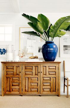 White walls, wood cabinet, tan rug, and large blue planter