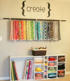 Storing fabric - check out the fabric hanging on the wall...clever way to use it as art and keep it readliy available too.
