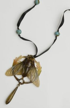 An Art Nouveau carved horn pendant. Modelled to depict a cicada fly with outstretched wings, heightened in graduating shades of green and brown, framed by foliage and suspending a tear-shaped drop below, to later ribbon suspension with turquoise-coloured paste bead spacers.