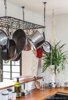 Armários pretos e paneleiro de ferro suspenso na cozinha dessa casa.