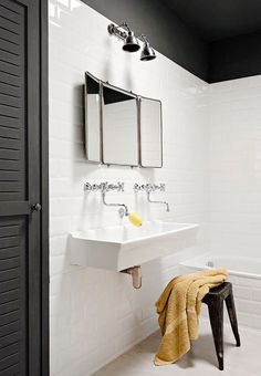 White bathroom with two faucets in the sink