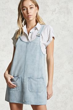 A denim overall dress featuring single button shoulder straps and front patch pockets.