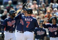 Denard Span #2, Justin Morneau #33 and Jamey Carroll #8 of the Minnesota Twins congratulate Joe Mauer #7 on a three run home run against the Los Angeles Angels of Anaheim during the fifth inning on April 12, 2012