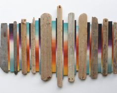 Wood wall art title: Sky and Earth This sculpture really pulls a feeling of the salt & sea inside. The driftwood is salvaged from the Jurassic coast of Dorset - south England. Once my materials have been hauled back to my studio, I begin selecting pieces for size and character. The straight clean, colourful reclaimed wood nicely off sets the rugged characterful driftwood.  The colours Ive picked for the piece are a simple gradient from a summer sky to a sumptuous red with a twist of black...