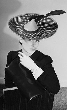The 1940 collection of Lilly Dache, New York millinery stylist, is this Breton of navy and white polka-dotted foulard. The brim is piped with bright red, matching the shooting quill and the funnel-shaped crown.