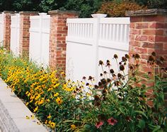 There is just something so special about this white fence with the brick columns. It's a nice callback to older home styles, yet it doesn't look outdated. Plus, I love that there aren't huge gaps in the fence. I'd feel much better about letting my kids play outside without supervision with a fence like this.
