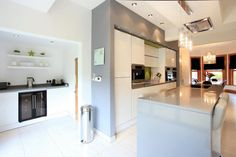 A stylish family kitchen with high gloss doors, Quartz worktops and Miele appliances. Designed and Fitted by Earle and Ginger Kitchens