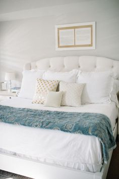 Traditional, luxurious and comfortable master bedroom with tufted white rounded headboard and bed frame, pale gray paint on the walls, crisp all-white bedding paired with metallic gold and white throw pillows and a burnout velvet paisley throw blanket. Love!