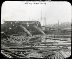 c. 1895. Lumber mill on the Penobscot River in the Bangor area. Logs would have been floated downstream to the holding pool, in the foreground, then logs guided up the ramps to the saws inside the mill.