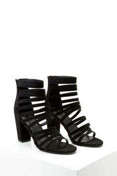 A pair of faux suede heels featuring a strappy design, open toe, zipper back, and a chunky heel.