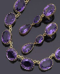 An amethyst necklace and pair of earclips The necklace designed as a slightly graduating line of collet-set oval-cut amethysts, the pendent earclips en suite, necklace length 45.7cm.