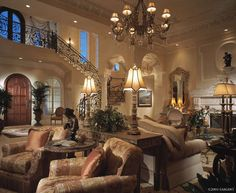 What's not to like in this traditional living room?  I love the iron railing on the staircase that goes back across the front of the house, the gorgeous ceiling treatment and columns, and the lovely furniture and accessories!