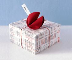 Wrap a package using Chinese takeout menus. For the fortune cookie, trace a circle onto crafts foam and cut out. Fold the foam circle in half. Hold the outer edges together, and push in the center of the foam until the edges meet. Tape to secure. Insert a strip of paper with gift recipient's name. Tape cookie to top of package.