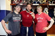 JANUARY 11: Alex Ovechkin #8 of the Washington Capitals poses with the puck commemorating his 1000th career NHL point from his first period goal with teammates Nicklas Backstrom #19 and T.J. Oshie #77