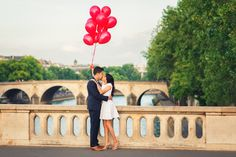Cute couple kissing on Louis Philippe bridge in Paris, during their engagement photo shoot, captured by Fran Boloni Paris engagement photographer