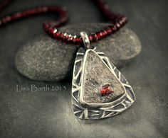 This is an interesting stone.  It is natural garnet in schist.  I carved a texture plate to go with this stone, to add some contrast in the setting.  The stone is bezel set in fine silver metal clay.