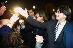 Former President of Catalonia Artur Mas (C) and new President of Catalonia Carles Puigdemont (R) shake hands with wellwishers after the parliamentary session debating on electing Carles Puigdemont as the new President of Catalonia on January 10, 2016 in Barcelona, Catalonia.
