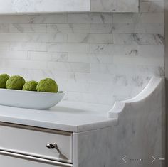 Suzie: de Giulio Kitchen Design - Gorgeous kitchen with white cabinets and marble subway tiles ...run the counter material around to the floor