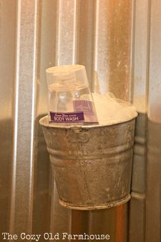 Galvanized shower walls and bucket for holding shower supplies.