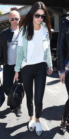 Kendall Jenner wears a white t-shirt, colorblocked motorcycle jacket, black pants, slip on sneakers, and a black duffle bag