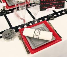 Afin de ne pas gâcher le superbe effet offert par le chemin de table, les verres à vin et les flûtes à champagne sont transparents. Superposées, les assiettes en plastique sont bordeaux et grises.