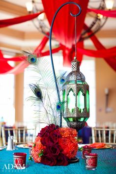Indian centerpiece-red roses, orange dahlias, and peacock feathers decorate the base of the shepherd hook