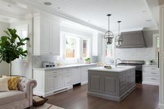 Transitional Gray and White Kitchen ll This transitional kitchen features carrara marble countertops and tile backsplash, a gray island with prep sink, and professional cooktop range with gray hood.  #Interiors #Decor #Grey fairylights.com
