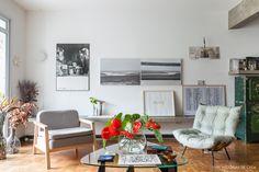 Sala de estar tem parede galeria, móveis vintage e banco de concreto.