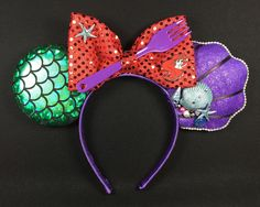 Little Mermaid Inspired Mickey Ears Version 2. I got the idea for these ears from a version I found here on Pinterest. My modifications are minimal, mostly having to do with the choice of materials for the purple shell shaped ear and the addition of blue shells and baubles. My DIY Mickey Ears by NMazzie