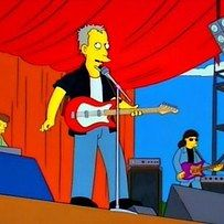 """Peter Frampton in """"Homerpalooza."""" Frampton comes to town to play Homer's music fest but gets mad when Homer destroys his large inflatable pig, Cypress Hill steal his orchestra and Sonic Youth and Marge steal food from him."""