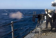 Petty Officer 3rd Class Austin Snow and Seaman Luke Lopez-Yolius fire a M2HB .50 Cal on a high speed maneuvering surface target from the USS Princeton (CG 59) during an exercise in the Pacific Ocean.