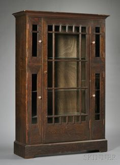 Arts & Crafts Bookcase  Oak and glass  Possibly Shop of the Crafters, c. 1912  Shaped top molding over center door flanked on each side by two doors, all with mullion overlay, raised on rectangular base, original metal pulls missing, has glass knob pulls, some wear, ht. 64, wd. 43, dp. 13 1/4 in.
