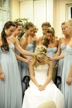 bridesmaids praying with the bride before the wedding :)