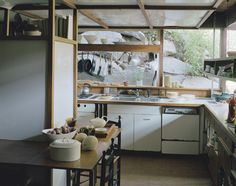 Sculptor, ceramist, and tableware designer Russel Wright built his home in Garrison, New York, in the 1950s. Design influences from Japan stemmed from a trip to Asia in 1955. The kitchen, shown here, features windows that look out upon rocks that lead up to Wright's studio. The ceramics are nearly all of his design.