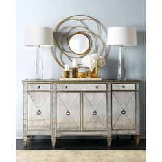 Reflective console with multiple storage options. Made of hardwoods and mirrored veneers. Painted silver finish with golden antiqued-glaze highlights. Three dr…