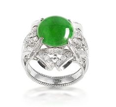 A jadeite and diamond ring Set with a bright green circular jadeite cabochon of good translucency, measuring approximately 11.2-11.2 x 3.5mm, within an openwork scrolling surround, set with brilliant and baguette-cut diamonds, mounted in 18k white gold, the diamonds estimated to weigh approximately 0.70 carats in total,