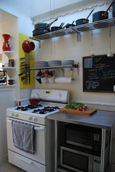 apartment therapy: small kitchen solutions - canisters on wall above stove to hold cooking utensils & papertowels, chalkboard, stainless steel countertop or shelving unit, s-hooks for hanging candles or sand-terrariums with air-plants