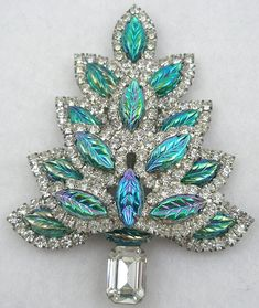 "Molded Glass Leaves Christmas Tree Brooch - Christmas tree brooch made with layers of iridescent blue-green aurora molded glass leaves, all the leaves but two are outlined with a row of clear rhinestones. The truck is a large rectangular clear rhinestone. An unusually large silver plated tree, both bold and glitzy. Size:  3 1/2"" x 2 5/8"" Z"