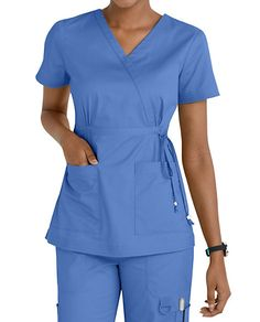 The Koi Katelyn Mock Wrap Top is stylish yet affordable top is highlighted by its flattering mock wrap design with a drawstring waist! Includes roomy pockets for your accessories. Medium center back length 27 Cute Nursing Scrubs, Cute Scrubs, Nursing Clothes, Green Scrubs, Koi Scrubs, Scrubs Outfit, Scrubs Uniform, Discount Scrubs, Professional Outfits