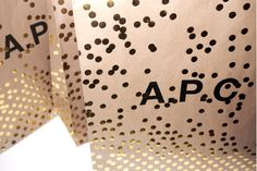 A.P.C. GIFT BAGS Brown kraft paper gift bags with gold foil-stamped dot pattern.