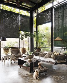 At decorator Gwynn Griffith's home in San Antonio, Texas, forest-green shades hang in the double-height screened porch. The suspended sofa and wicker chair are accessorized with pillows covered in African textiles, and the side table is by John Dickinson; stained concrete floors nod to the building's industrial past.    - ELLEDecor.com