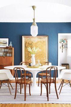Dining room with a blue contrast wall, a retro chandelier, a framed vintage map, and a large marble dining room table